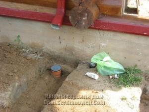 Горловина трубы выходит из земли прямо под водосточкой