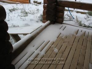 Пол на террасе с провалившимся в щели снегом
