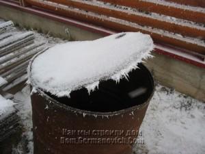 Крышка железной бочки украшена морозом